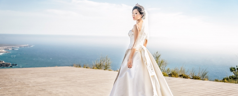 Asian bride standing in beautiful coastline photographed by wedding photographer Sharron Goodyear